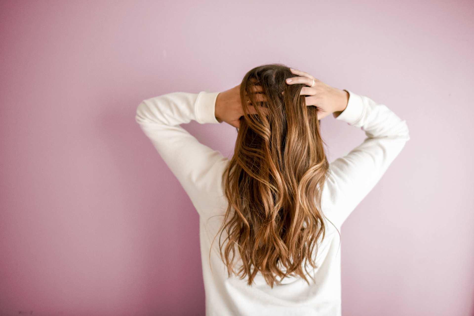 kobieta obrócona tyłem z dłońmi we włosach